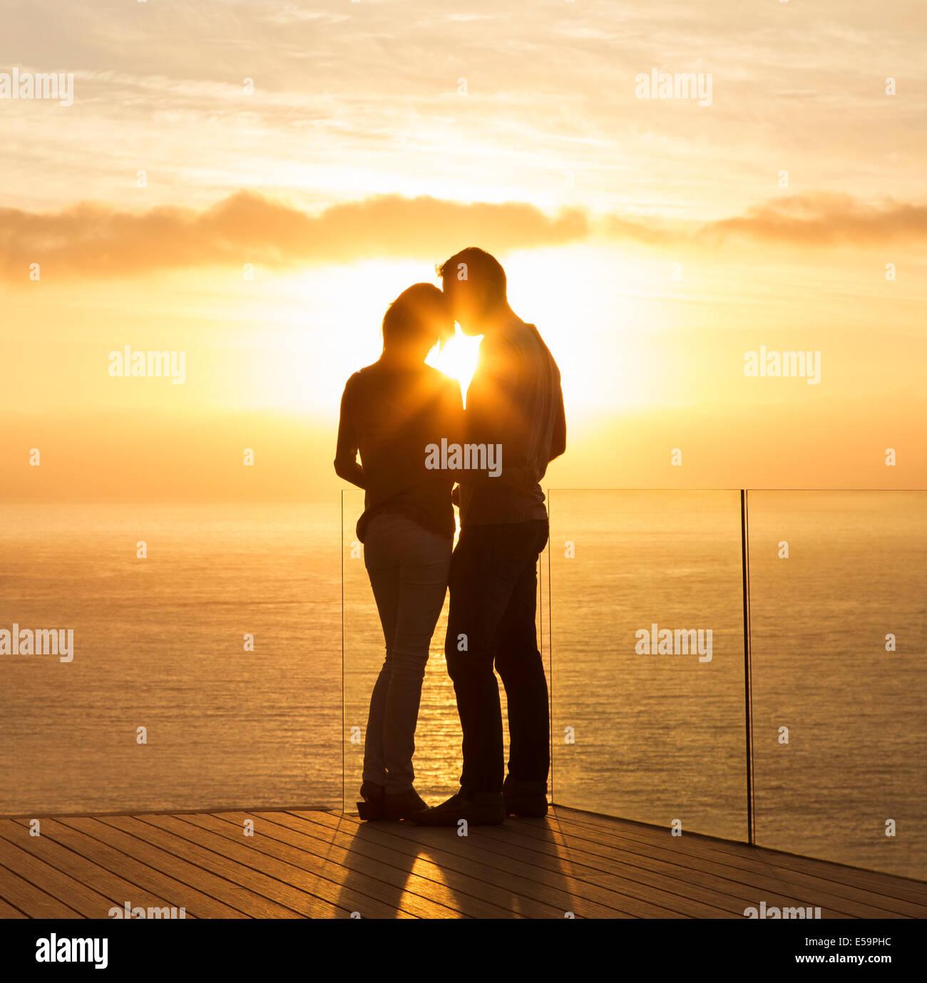 Silueta de la pareja durante la puesta de sol sobre el océano Imagen De Stock