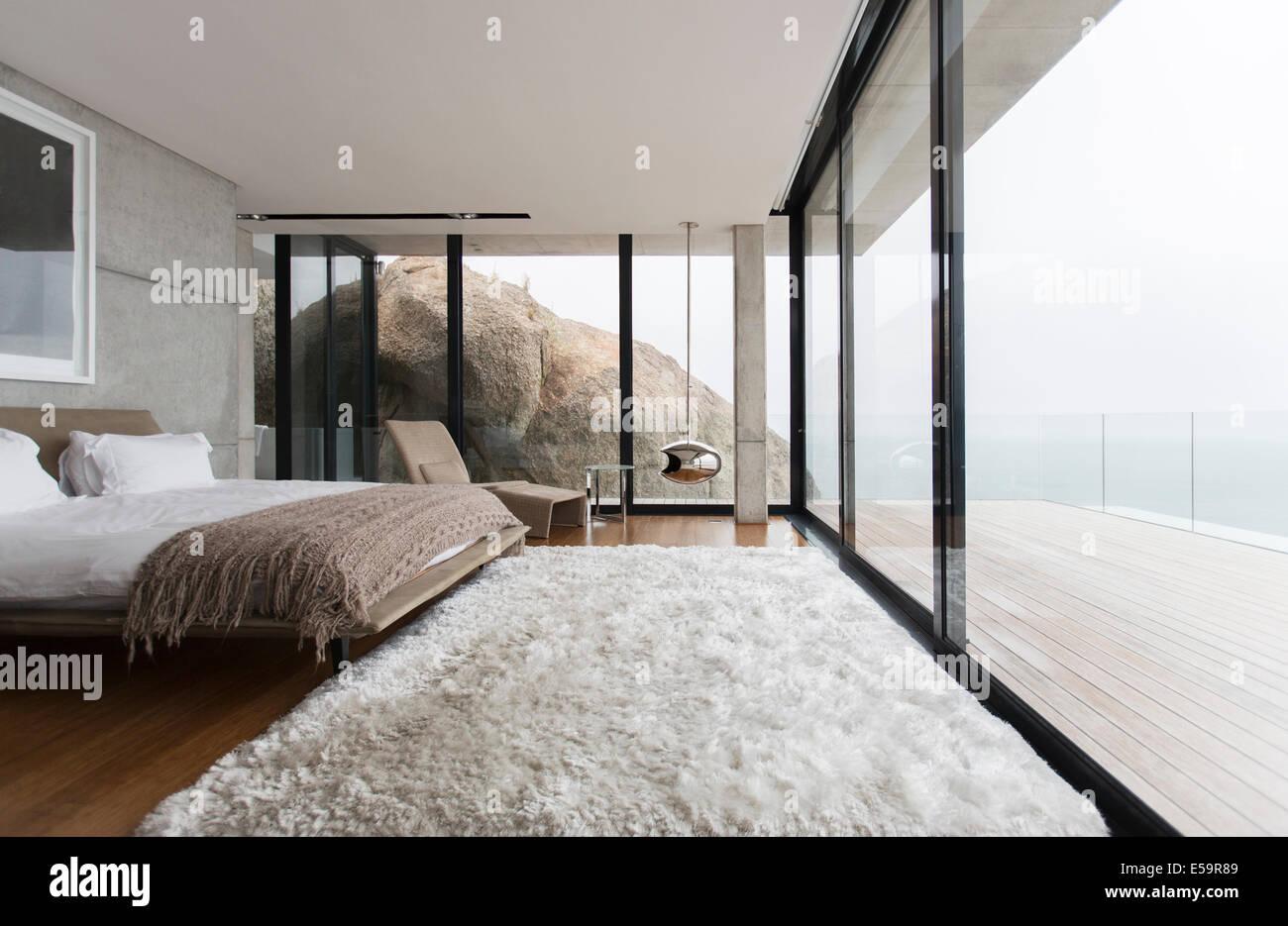 Shag rug y paredes de vidrio en dormitorio moderno Foto de stock