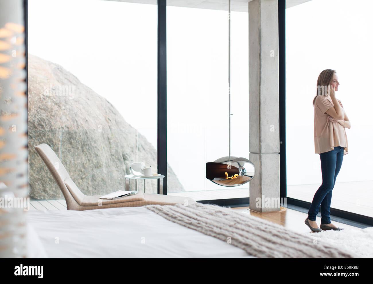 Mujer hablando por teléfono celular en el dormitorio moderno Imagen De Stock