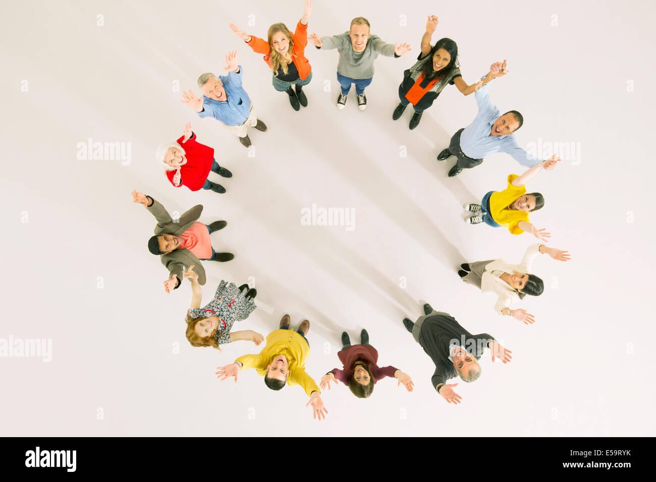 La gente de negocios con los brazos levantados en círculo Imagen De Stock