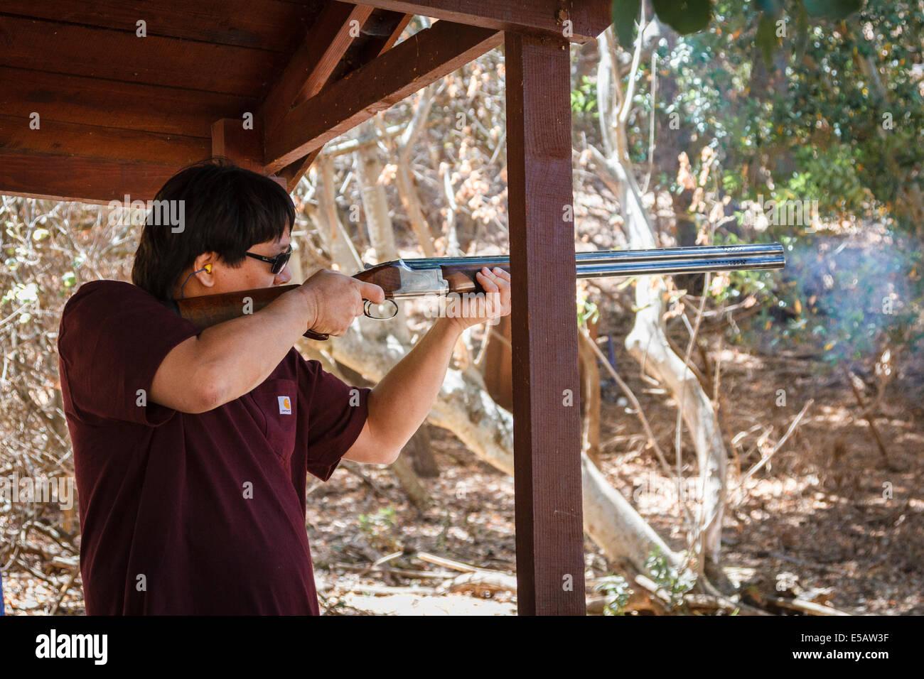 Asian American man shooting arcillas con humo saliendo de su escopeta Imagen De Stock
