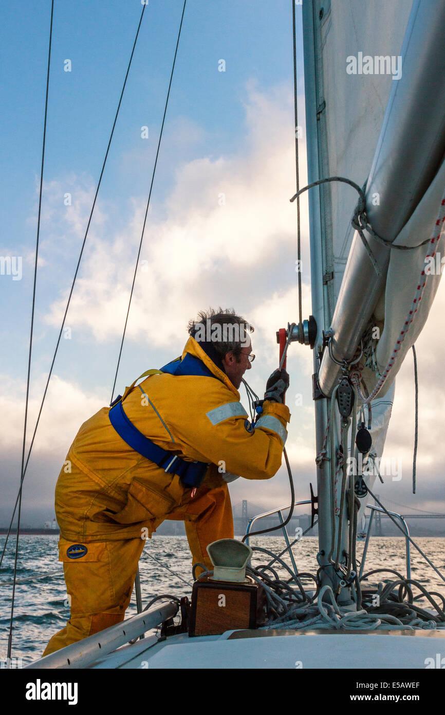 Marinero en amarillo ropa impermeable que fijan la driza después de subir la vela mayor partida en tiempo nublado Imagen De Stock