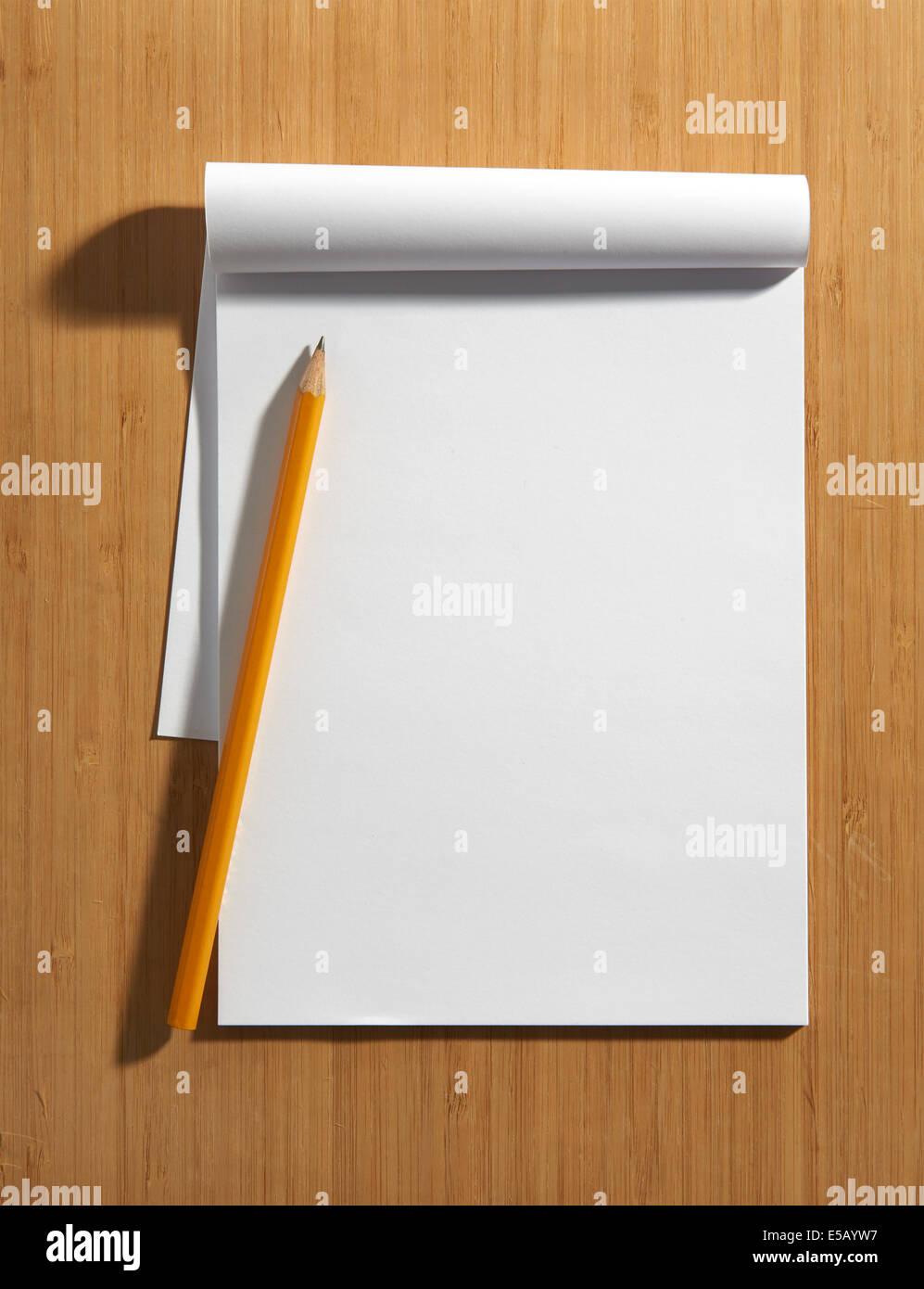 Vista aérea de una página en blanco de un bloc de notas con copia espacio y un lápiz tumbado sobre Imagen De Stock