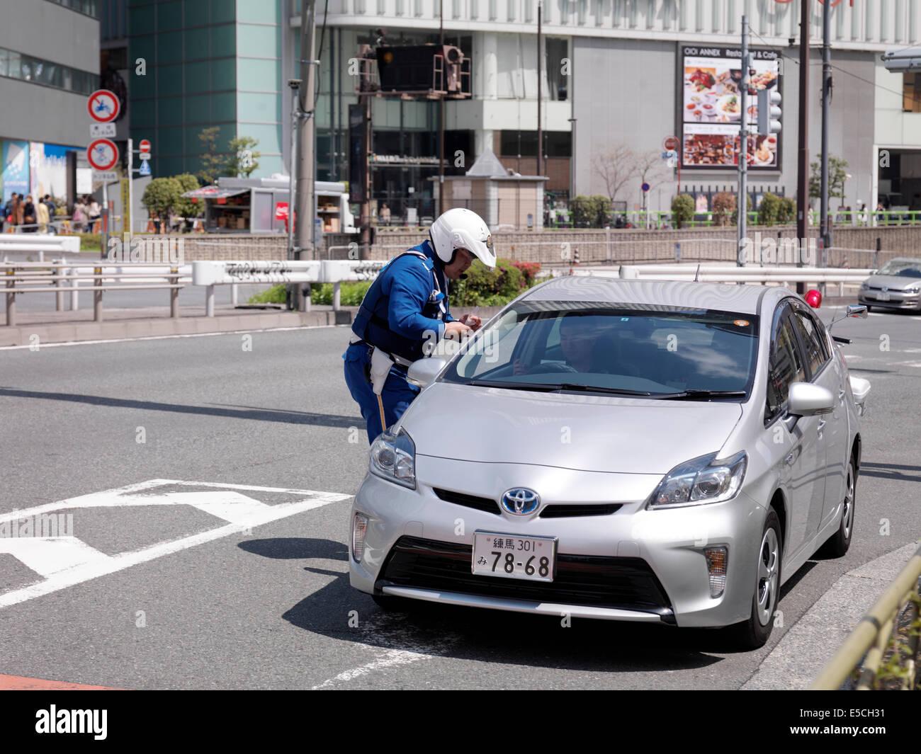 Oficial de policía comprobando la licencia de conducir de un conductor en un coche parado. Tokio, Japón. Imagen De Stock
