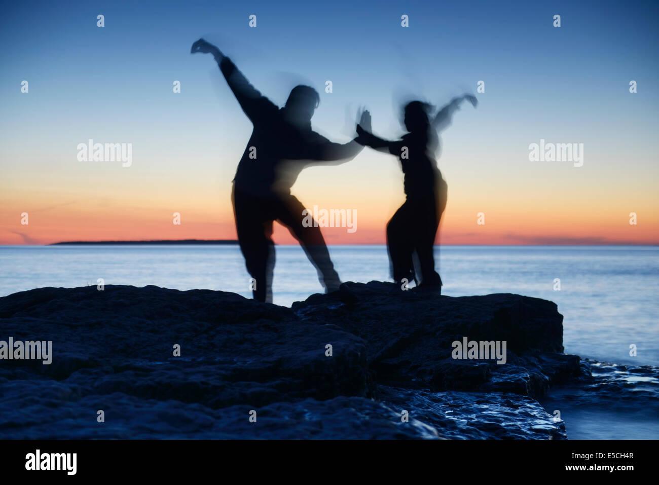 Dos siluetas borrosas de gente que practica artes marciales al atardecer en la naturaleza más colorido cielo Imagen De Stock