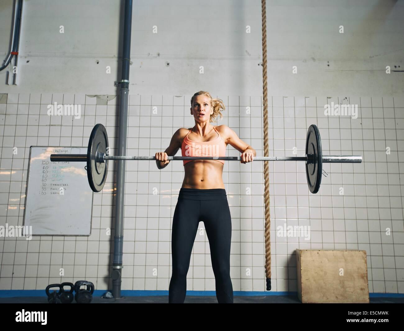 Joven Mujer fuerte cruz prácticas encajan en un gimnasio. Colocar mujeres sosteniendo un barbell con pesos Imagen De Stock