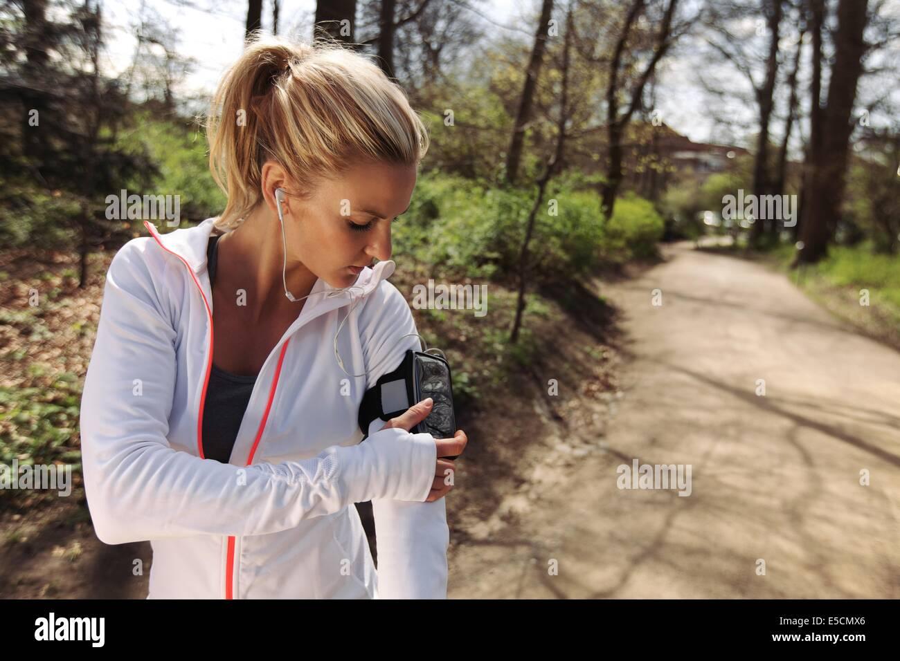 Hermosa joven formación al aire libre mientras usa un smartphone para supervisar su progreso. Corredoras del Imagen De Stock