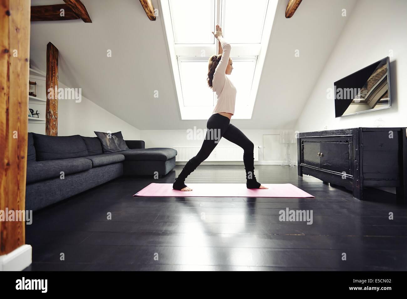 Colocar joven hacer yoga en casa. Modelo femenino sano ejercicio en casa viva. Imagen De Stock