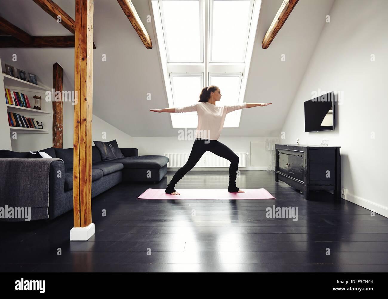 Imagen de longitud completa de fit mujer de pie sobre la colchoneta de ejercicios con los brazos extendidos haciendo Imagen De Stock