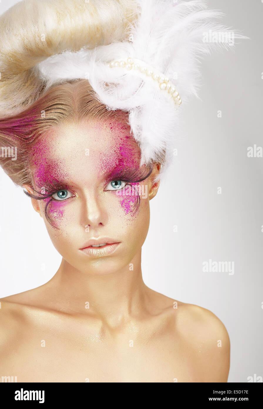 Mujer con plumas vistosas difusa y Arte fantástico maquillaje Imagen De Stock