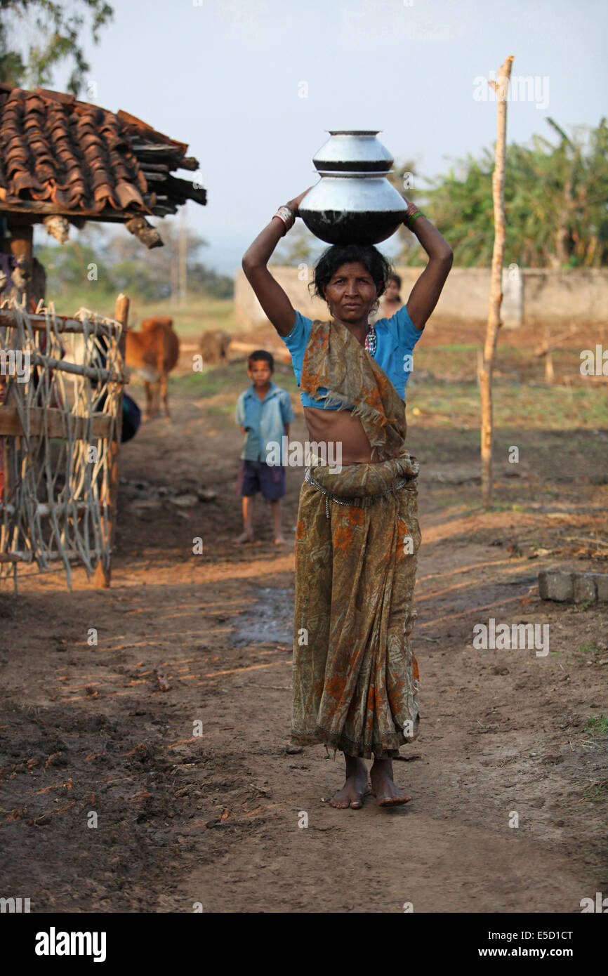Mujer Tribal llevar utensilios en su cabeza, Baiga tribu, Aldea, Chattisgadh Karangra, India Foto de stock