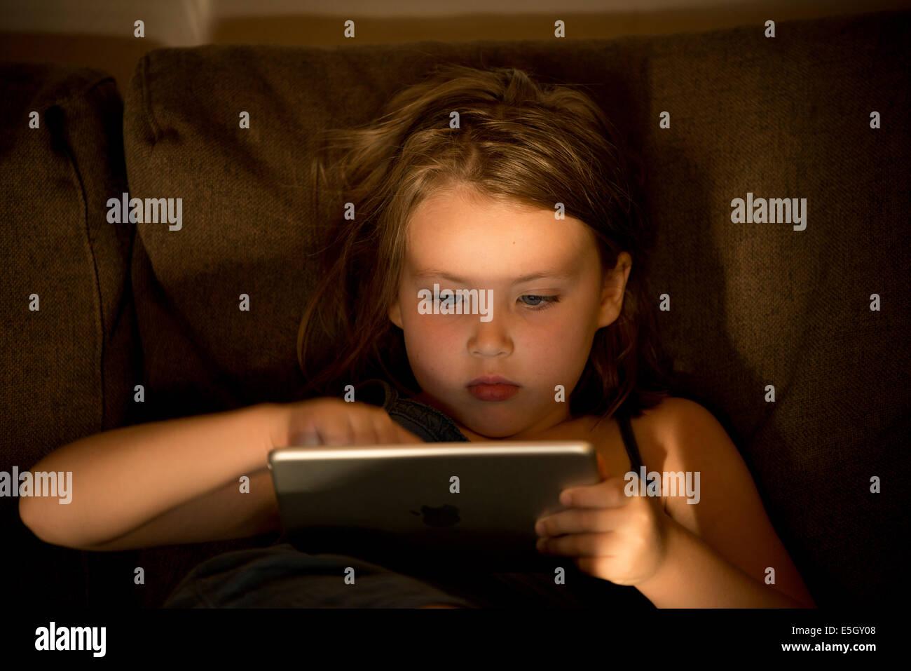 Niña de seis años con un ipad mini tablet PC en casa. Imagen De Stock