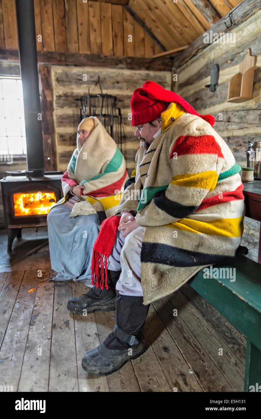 Una pareja voyageur mantenerse caliente por un woodstove fuego, Festival du Voyageur, Winnipeg, Manitoba, Canadá Imagen De Stock