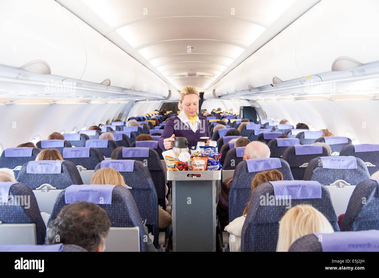Monarch Airlines, azafata aérea que sirve aperitivos del carrito de bebidas, Reino Unido Foto de stock