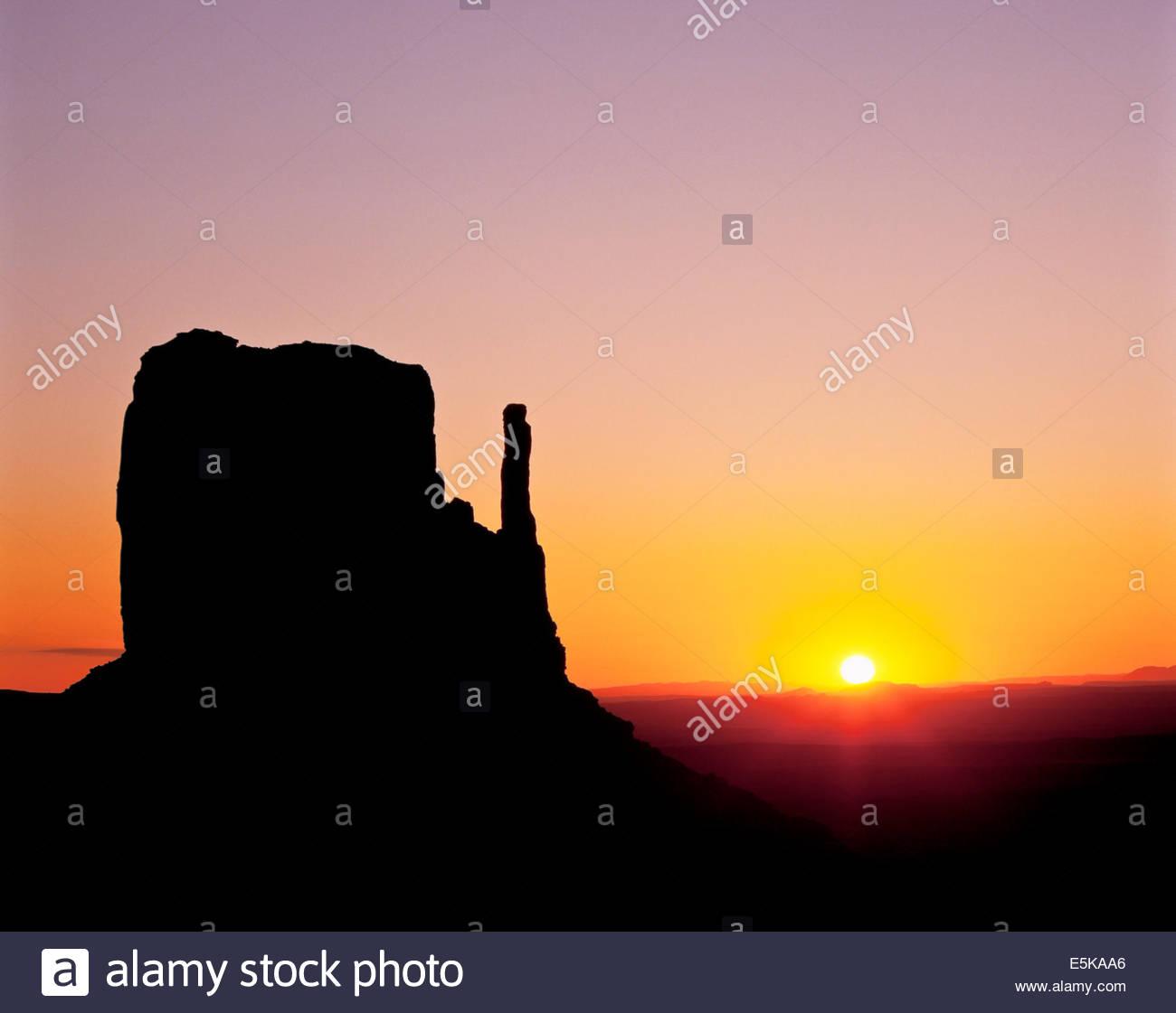 Amanecer detrás del oeste mitten butte en Monument Valley Navajo Tribal Park, en la Reservación Navajo Imagen De Stock