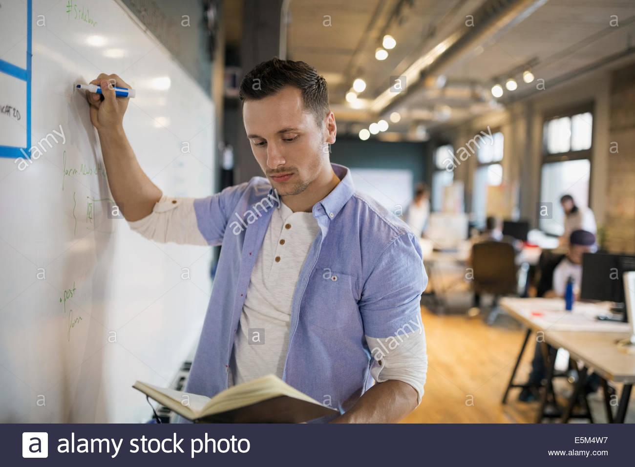 Empresario con libro escrito en pizarra en Office Imagen De Stock