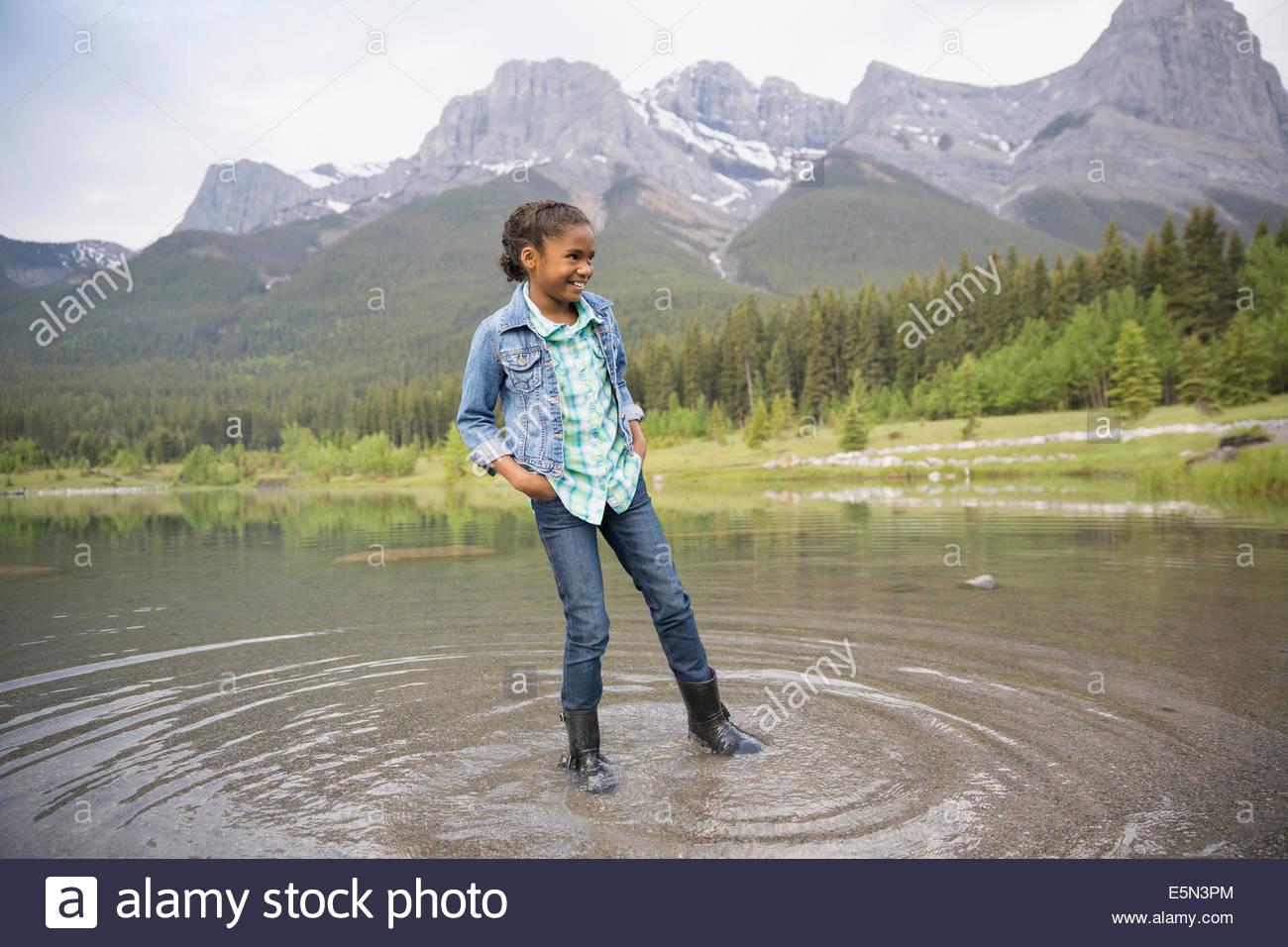 Niña jugando en el lago con las montañas en el fondo Imagen De Stock