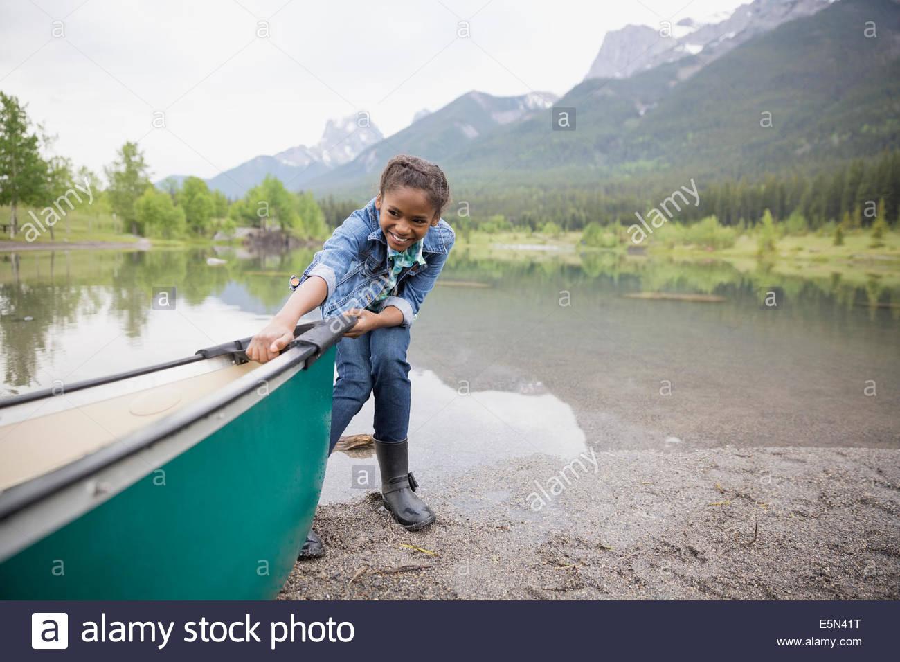 Chica tirando de canoa en el lago Imagen De Stock