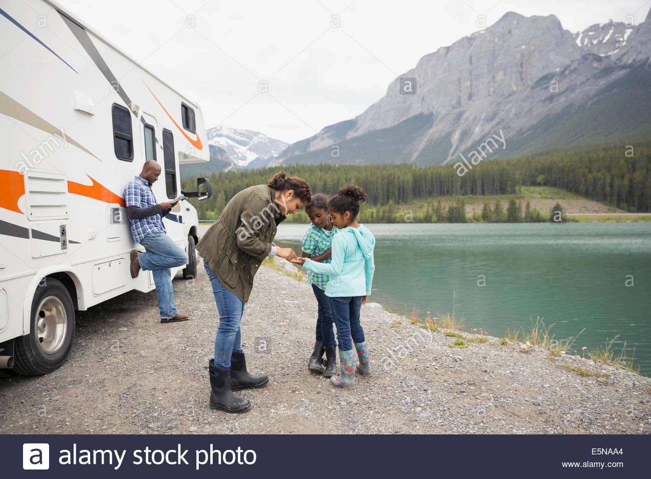 Familia de pie en lakeside cerca de RV Foto de stock