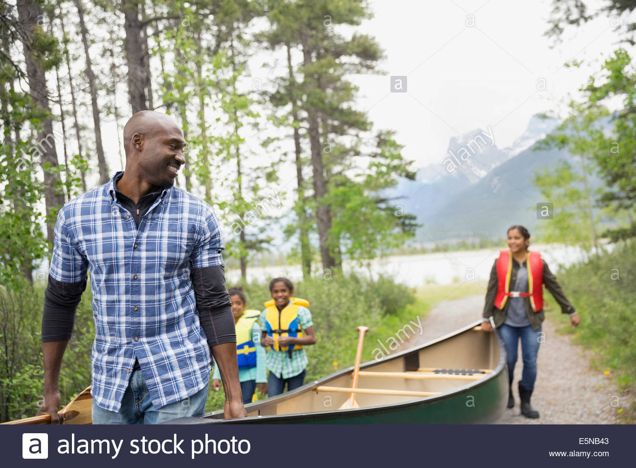 Familia llevar canoa lejos del lago Imagen De Stock