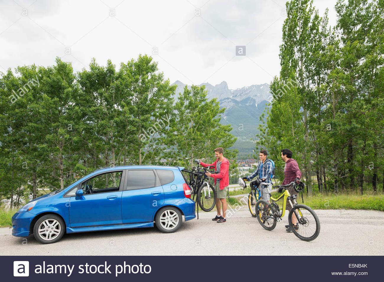 Los hombres quitando las bicicletas de portabicicletas en coche Imagen De Stock