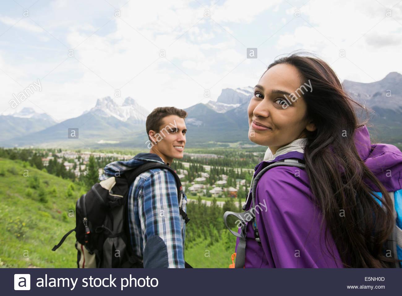 Pareja con mochilas senderismo cerca de las montañas Imagen De Stock