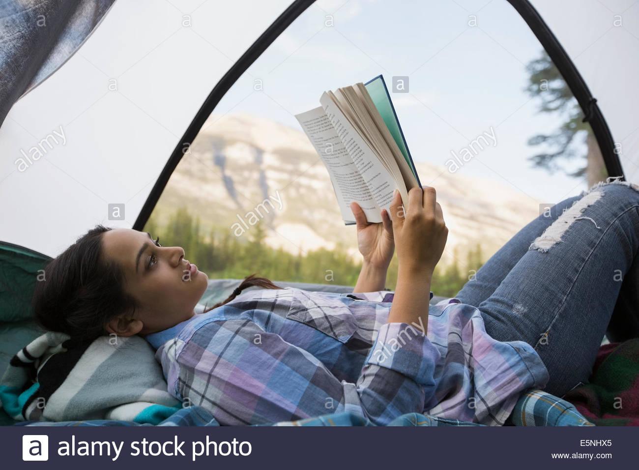 Mujer leyendo el libro en la carpa con vista a la montaña Imagen De Stock