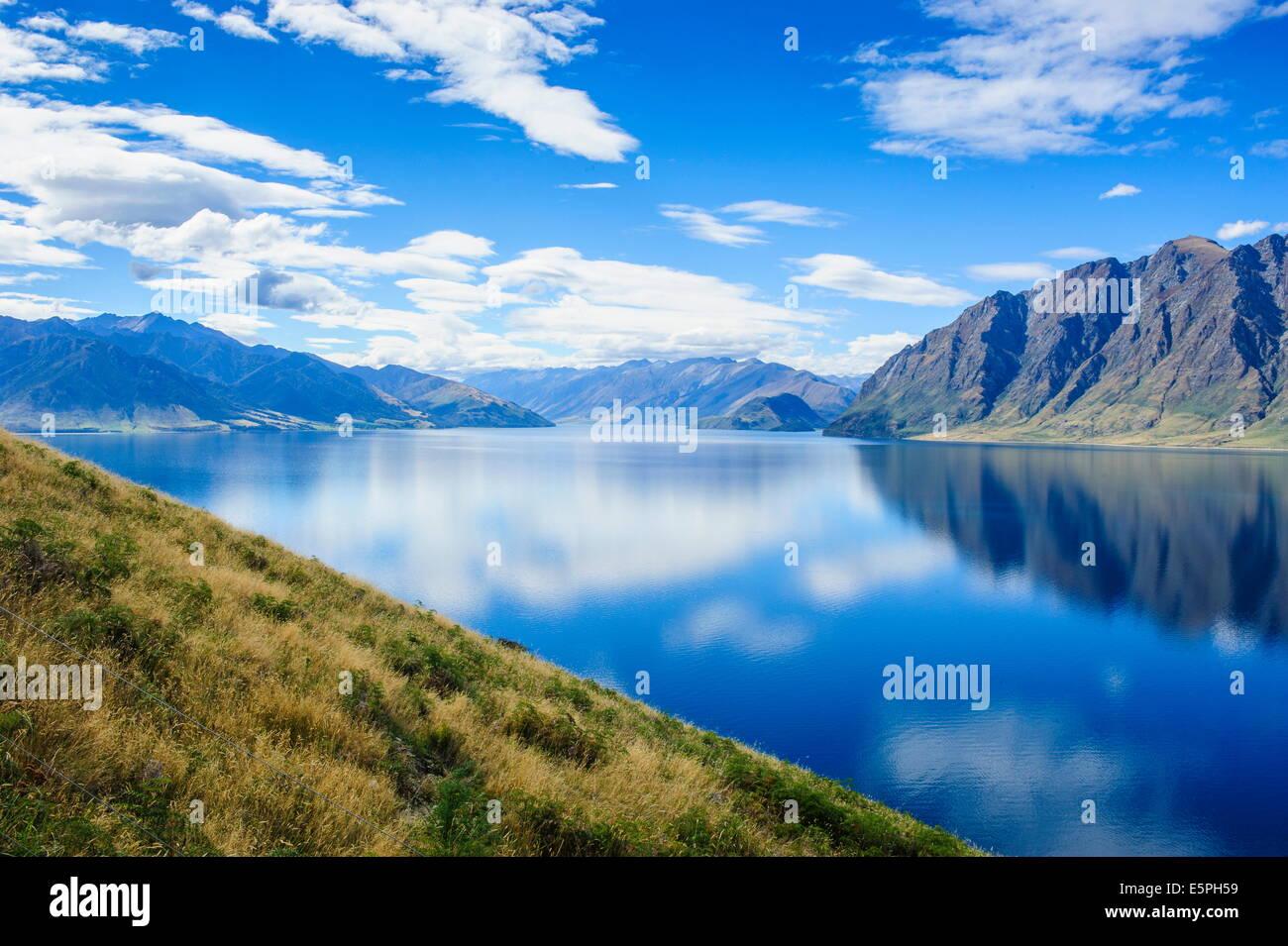 Reflexiones de nube en el lago Hawea, Haast Pass, Isla del Sur, Nueva Zelanda, el Pacífico Imagen De Stock
