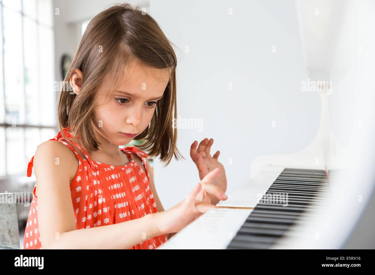 Niña de 5 años tocando el piano. Imagen De Stock