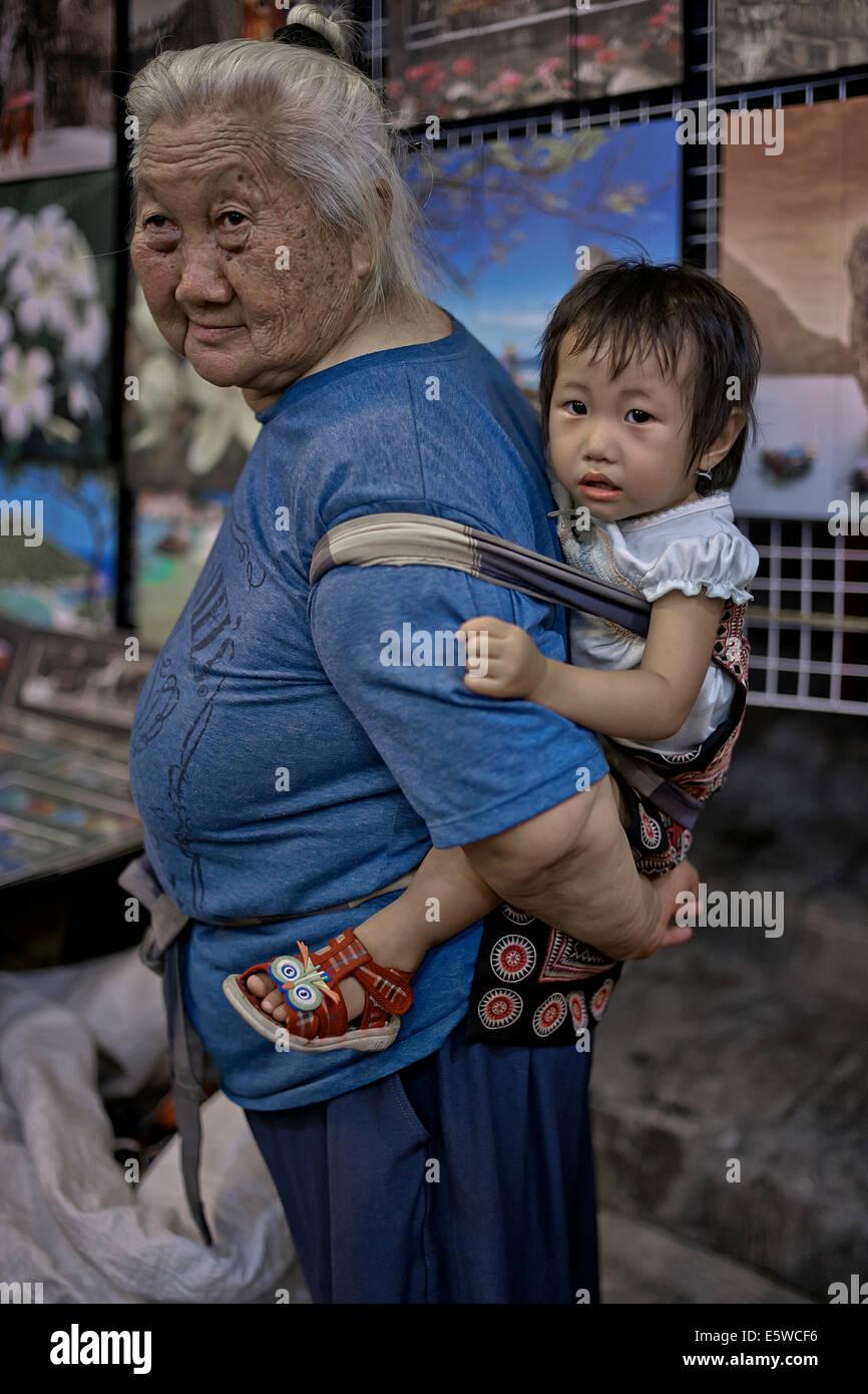 Abuela tailandés llevando bebé nieta en un arnés eslinga. Tailandia S. E. Asia, Asia grandma transportaba niños Foto de stock