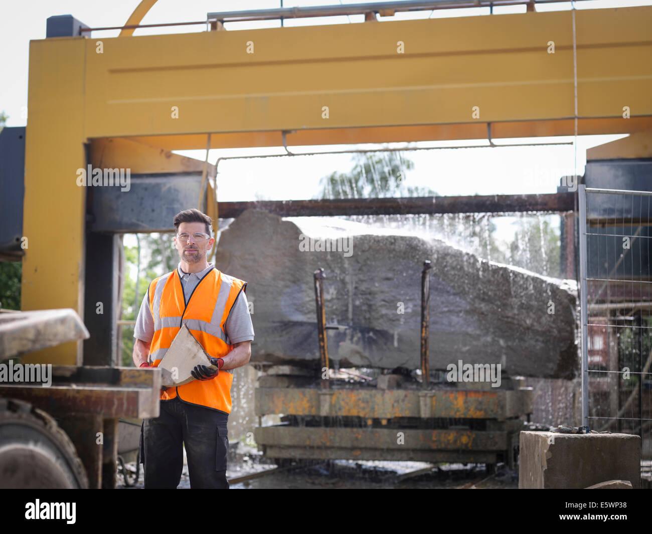 Retrato de cantera trabajador en frente de gran roca cortada en sierra de piedra Imagen De Stock