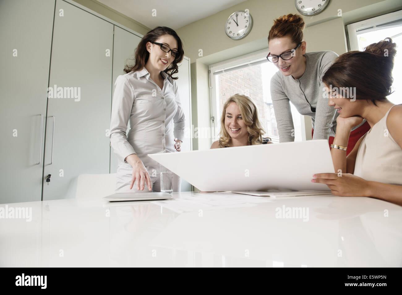 Cuatro mujeres diseñadores mirando blueprint en Office Imagen De Stock