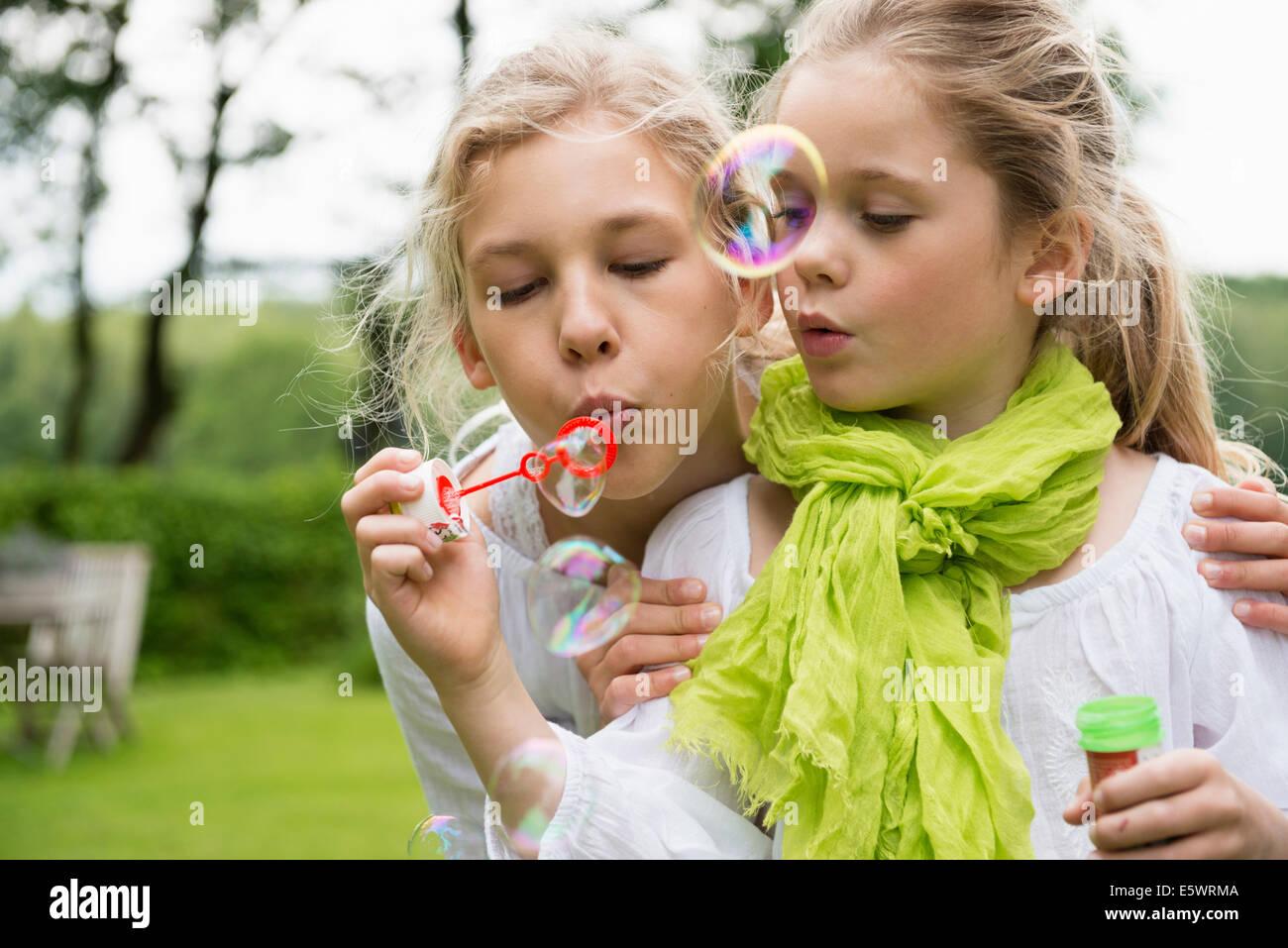 Dos hermanas soplando burbujas Imagen De Stock