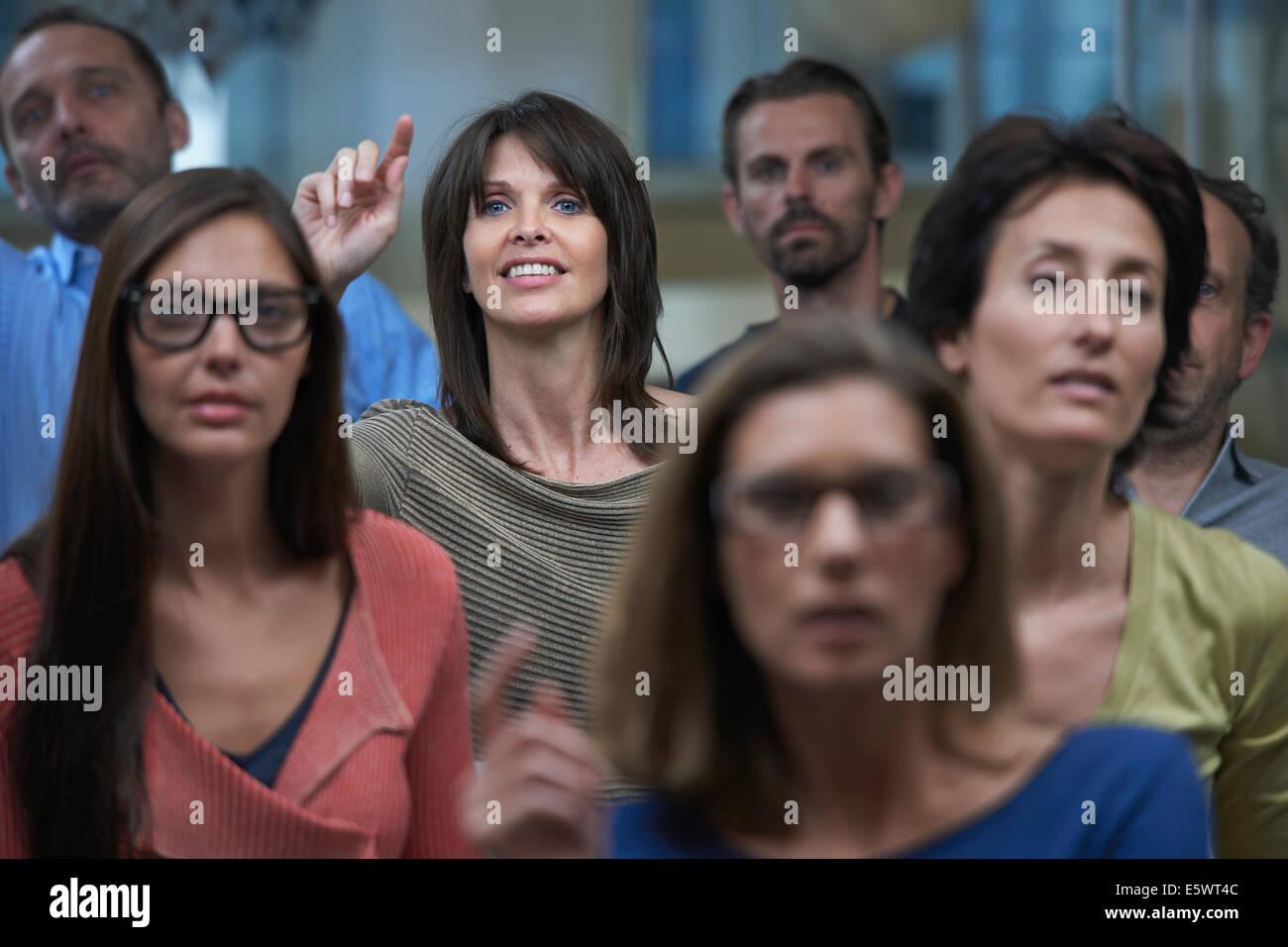 Grupo viendo la presentación, mujer levantando la mano Imagen De Stock
