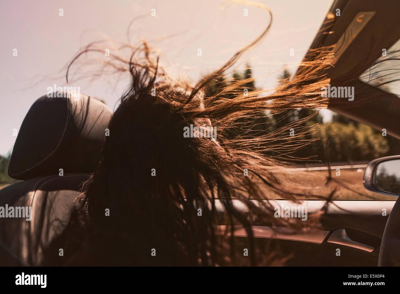 Mujer adulta media conduciendo convertible con pelo largo soplando en el viento Foto de stock