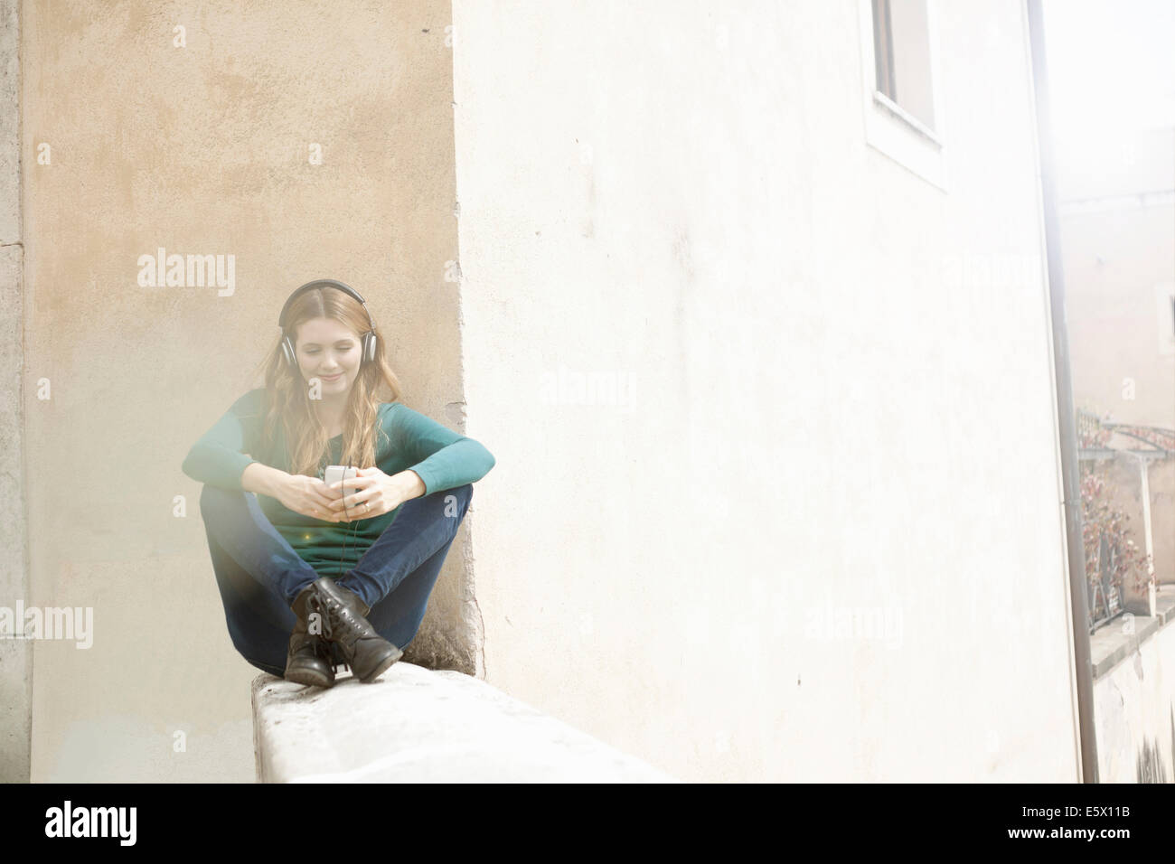 Mujer joven sentada piernas cruzadas escuchando música a través de auriculares Imagen De Stock