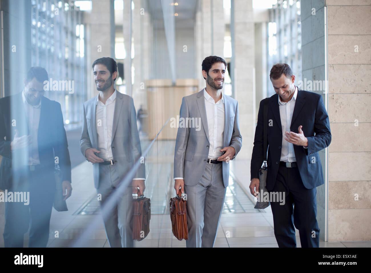 Dos jóvenes empresarios caminando y conversando en el centro de conferencias Imagen De Stock