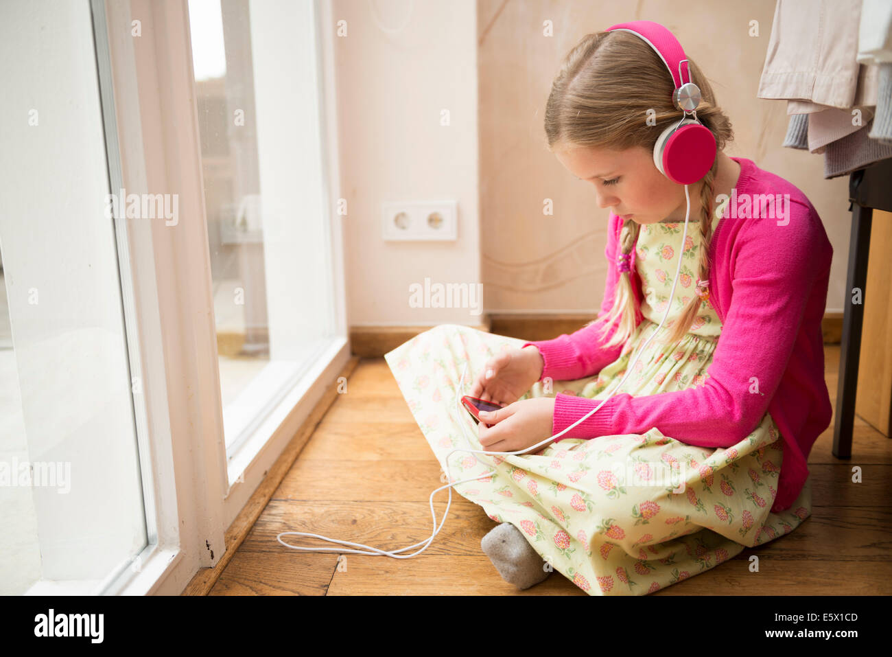 Chica sentada en el suelo Seleccionar música para auriculares Foto de stock