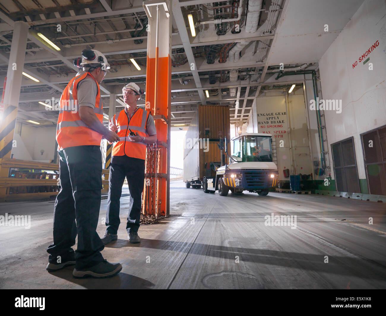 Los trabajadores portuarios de contenedores de carga en la bodega del barco Imagen De Stock
