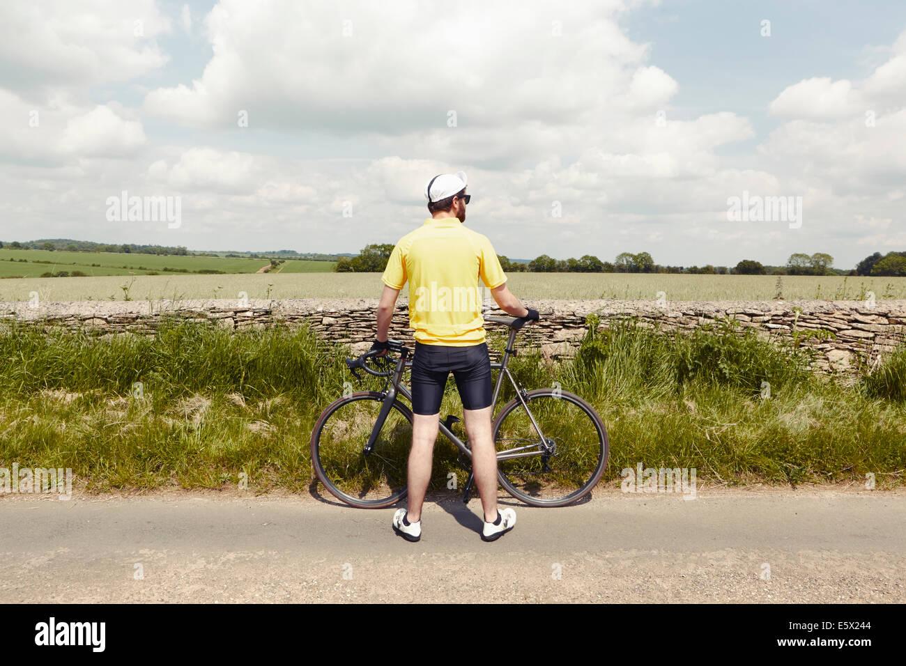 Ciclista parado por pared de piedra, Cotswolds, REINO UNIDO Imagen De Stock