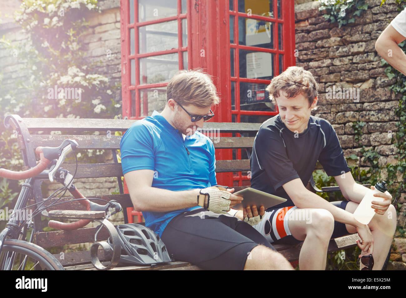 Los ciclistas utilizando digital comprimido por teléfono rojo cuadro, Cotswolds, REINO UNIDO Imagen De Stock
