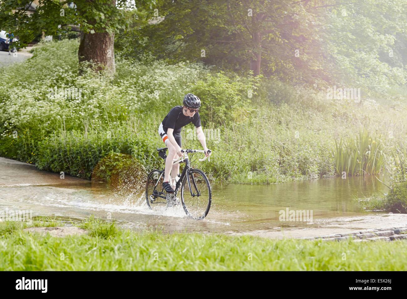 Equitación ciclista más camino inundado, Cotswolds, REINO UNIDO Imagen De Stock