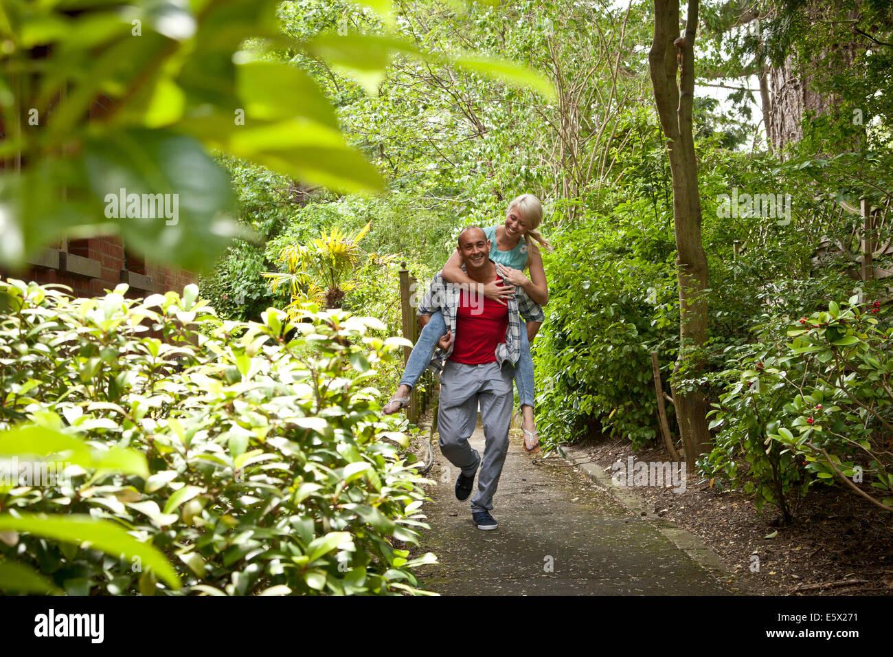 Feliz pareja divertirse dando piggy back en el jardín Foto de stock