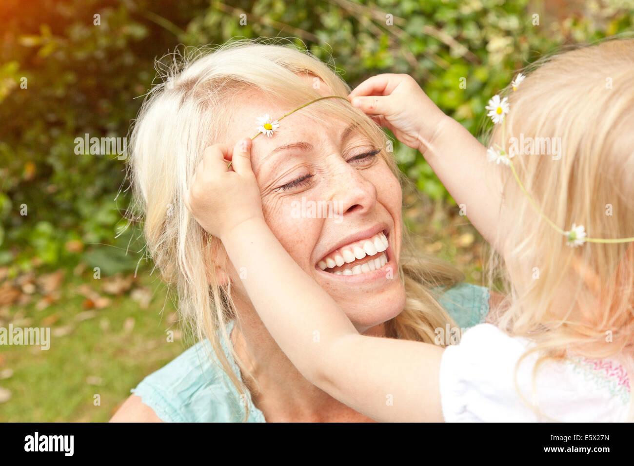 Cerca del infante femenino colocando daisy chain en el cabello de la madre en el jardín Foto de stock