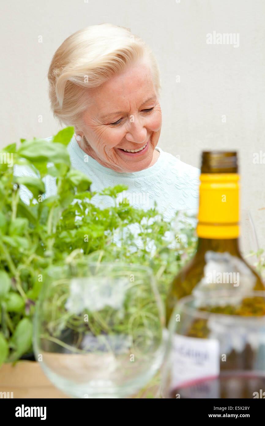 Senior mujer sentada en la mesa de jardín Imagen De Stock
