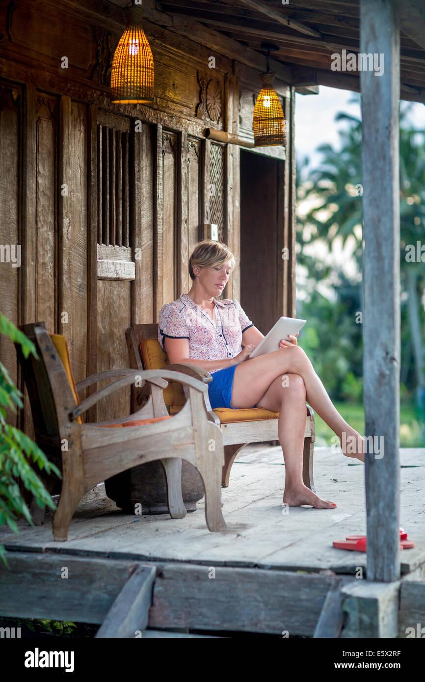 Mujer relajante con tablet digital de vacaciones Apartamento porche, Ubud, Bali, Indonesia Imagen De Stock
