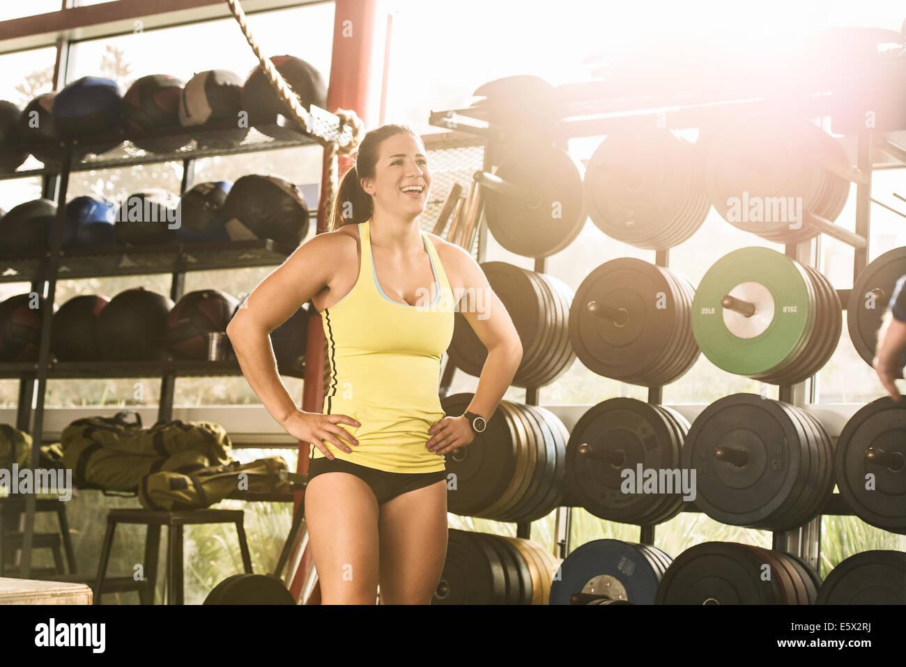 Feliz culturista de pie delante de un aparato de gimnasia Imagen De Stock