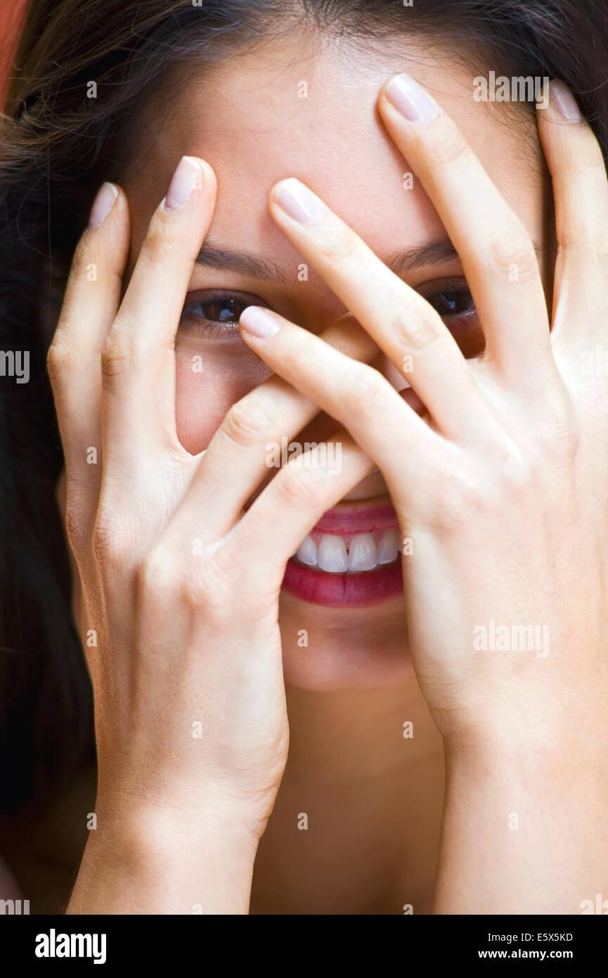 Retrato de mujer joven con las manos cubriendo cara Imagen De Stock
