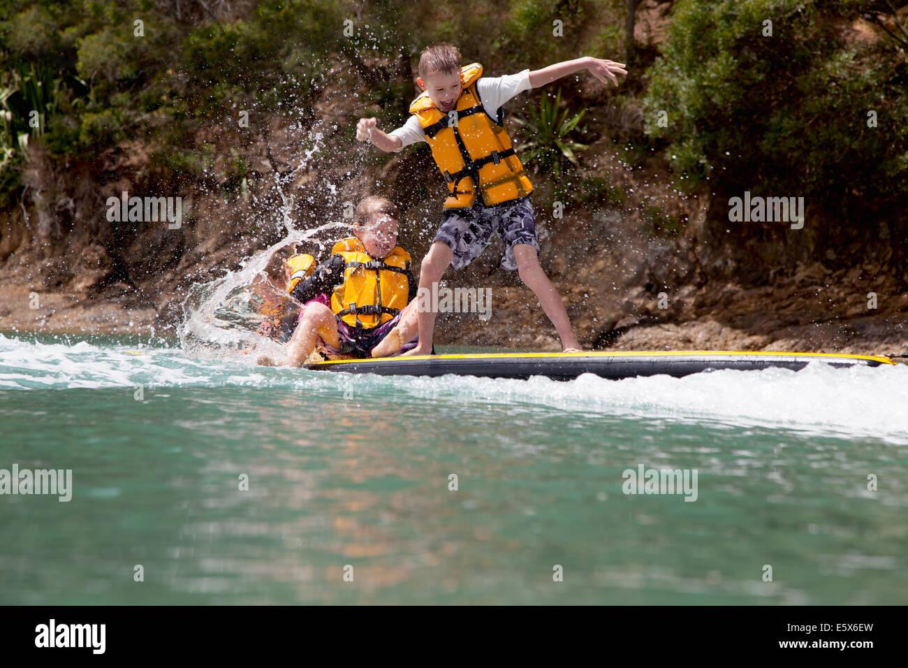 Hermanos y hermanas de paddleboard chapoteando en el mar Imagen De Stock