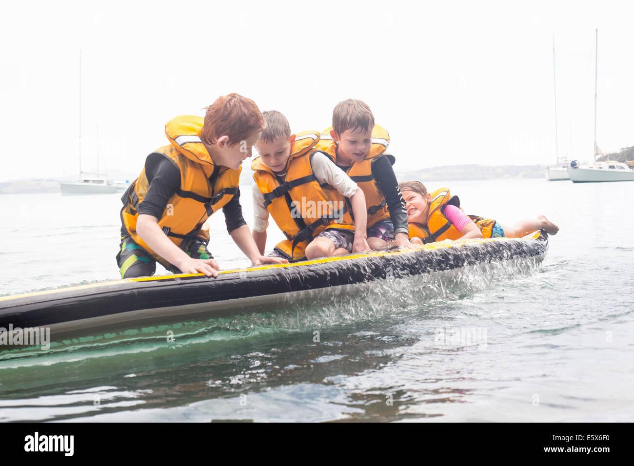 Hermanos y hermanas de paddleboard a punto de caer en el mar Imagen De Stock